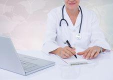 Doctor writing on clipboard on desk with digital world map in background Stock Images