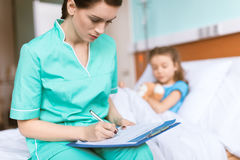 Doctor writing in clipboard diagnosis of sick little girl. Woman doctor writing in clipboard diagnosis of sick little girl Stock Images