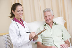 Doctor writing on clipboard giving checkup to man Royalty Free Stock Image