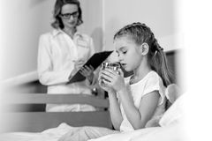 Doctor writing in clipboard while little girl patient taking medicines. Black and white photo Royalty Free Stock Images