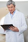 Doctor Writing On Clipboard. Mature male doctor writing on clipboard while standing next to CT scan machine Royalty Free Stock Image