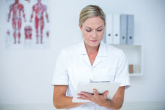 Doctor writing on clipboard Stock Photo
