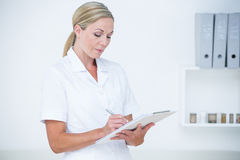 Doctor writing on clipboard Stock Photography