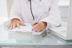 Doctor writing on a clipboard Royalty Free Stock Photos