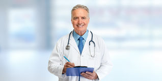 Doctor writing on clipboard. Medical doctor pharmacist man writing prescription on blue background Stock Photography