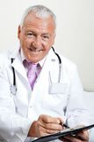 Doctor Writing On Clipboard. Portrait of senior male doctor smiling while writing on clipboard Royalty Free Stock Image