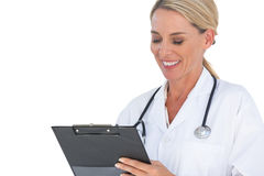 Doctor writing on a clipboard and smiling Stock Image