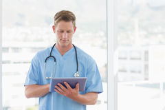 Doctor writing on clipboard beside windows Royalty Free Stock Image