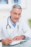 Doctor writing on diary at his desk Stock Photography