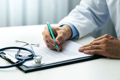 Doctor writing documents in clinics office Royalty Free Stock Images