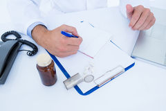 Doctor writing down on a notebook Stock Photo