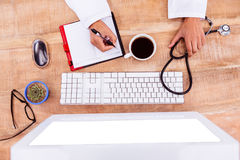 Doctor writing on her diary. On desk Royalty Free Stock Images