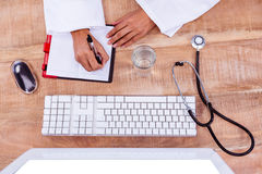 Doctor writing on her diary. On desk Stock Photo