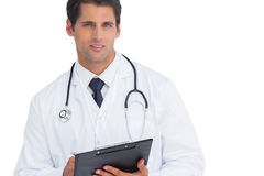 Doctor writing on his clipboard and looking at camera Stock Images
