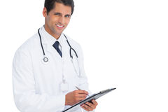 Doctor writing on his clipboard and smiling Royalty Free Stock Image