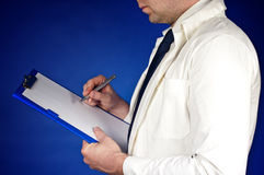 Doctor writing in his notebook  on blue Stock Photo