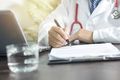 Doctor writing information to patient on medicine paper in clini. Doctor writing information to patient on medicine paper for planning to take care good healthty Royalty Free Stock Images