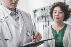 Doctor writing on medical chart with patient in the background Royalty Free Stock Photos
