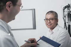 Doctor writing on medical chart with a smiling patient Royalty Free Stock Image
