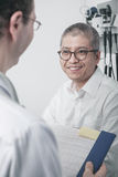 Doctor writing on medical chart with a smiling patient Stock Images