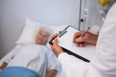 Doctor writing medical details of a senior patient Stock Images