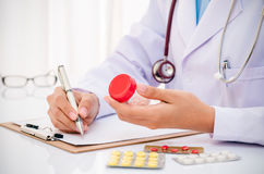 Doctor writing medical record Stock Image