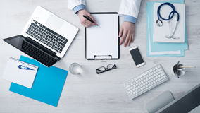 Doctor writing medical records. Professional doctor writing medical records on a clipboard with computer and medical equipment all around, desktop top view Royalty Free Stock Photography