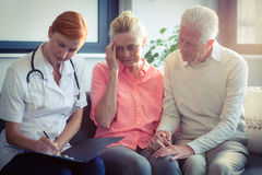 Doctor writing medical report of senior couple Royalty Free Stock Photography