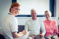 Doctor writing medical report of senior couple Royalty Free Stock Images