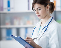 Doctor writing medical reports Stock Photos