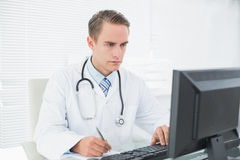 Doctor writing a note while using computer at medical office Stock Images
