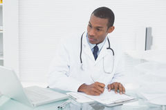 Doctor writing a note while using computer at medical office Stock Image