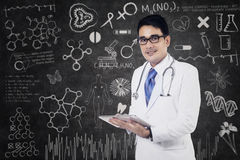Doctor is writing a note. Young male doctor is writing a note standing on class Royalty Free Stock Images
