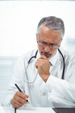 Doctor writing on notepad. At clinic Stock Photography
