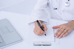 Doctor writing on a notepad stock photography