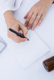 Doctor writing on a notepad Stock Images