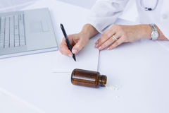 Doctor writing on a notepad Stock Photo