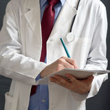 Doctor writing notes. Male doctor in white coat is writing notes in white notebook Royalty Free Stock Photo