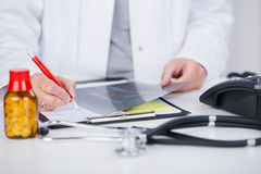 Doctor Writing Notes While Holding Xray At Desk Royalty Free Stock Image
