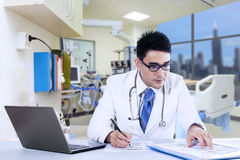 Doctor writing notes with laptop Royalty Free Stock Images