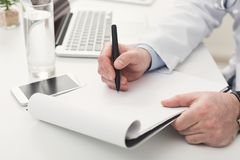 Doctor writing notes at office, closeup. Unrecognizable male doctor writing notes in clipboard while working at her office. Always ready to help, medicine Royalty Free Stock Photography