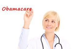 Doctor writing Obamacare stock image