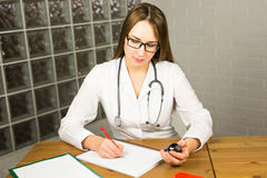 Doctor writing on paper at clinic Stock Photography