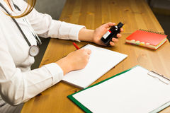Doctor writing on paper at clinic royalty free stock photo