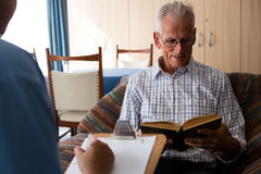 Doctor writing on paper while senior man reading book in nursing home. Female doctor writing on paper while senior men reading book in nursing home Stock Photography