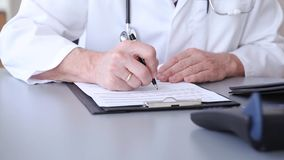 Doctor writing patient notes on a medical examination form. Or prescription