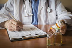Doctor writing patient notes on a medical examination Royalty Free Stock Images