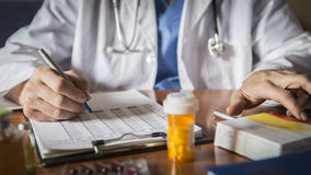 Doctor writing patient notes on a medical examination. Or prescription Stock Images