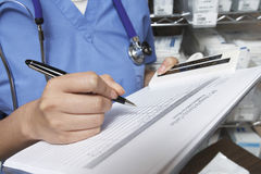Doctor Writing In Patient's Medical Chart Stock Images
