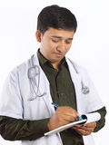 Doctor Writing Prescription. Indian Young Doctor Writing Prescription Royalty Free Stock Photography